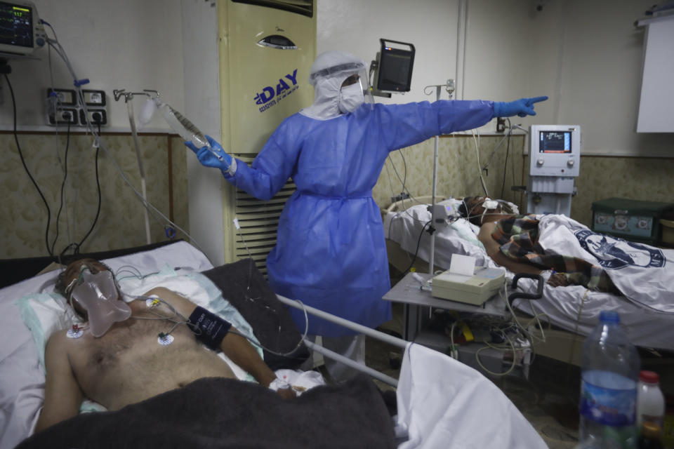 A medic works with corona patientsin a hospital in Idlib, Syria, Saturday, Nov. 14, 2020. At one of two coronavirus hospitals in Syria's rebel-held Idlib province, overwhelmed medical staff tend to patients drifting in and out of consciousness. As confirmed case numbers rise to as many as 500 a day, so does the demand for beds in the intensive care ward (AP Photo/Ghaith Alsayed)