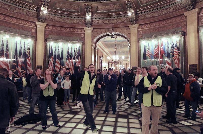 RETRANSMISSION FOR IMPROVED TONING--Union workers chant in the lower level of the Capitol rotunda in Lansing, Mich., Thursday, Dec. 6, 2012. Hundreds of chanting and cheering protesters streamed back into the Michigan Capitol after receiving a court order saying that the building must reopen. The pro-union crowd walked in as lawmakers were debating right-to-work legislation limiting union powers. The Republican-led House subsequently passed the bill with no Democratic support. (AP Photo/Carlos Osorio)