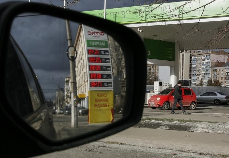 """A man walks past """"Amic"""" fuel stations displaying prices of 0.77 USD and 0.81 USD per litre of basic unleaded petrol during falling global oil price in Kiev, Ukraine, February 5, 2016. REUTERS/Gleb Garanich"""