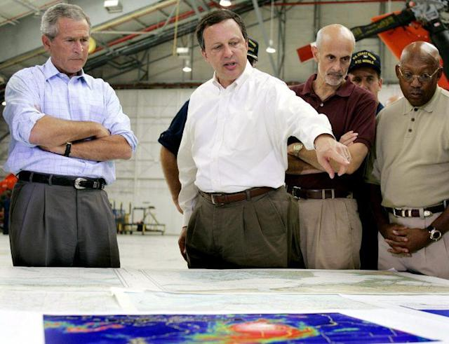 President George W. Bush and Homeland Security Secretary Michael Chertoff, second from right, get a briefing from Federal Emergency Management Agency chief Michael Brown, center, in September 2005 before touring the devastation left by Hurricane Katrina. (Photo: Jim Watson/AFP/Getty Images)