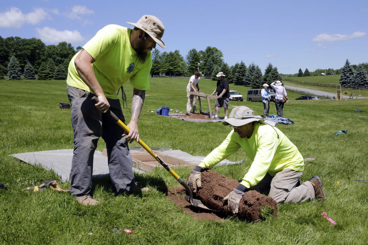 In this Thursday, June 14, 2018 photo, Jesse Pagels, left, and Edgar Alarcon, of the Public Archaeology Facility at Binghamton University, start a new dig at the site of the original Woodstock Music and Art Fair, in Bethel, N.Y. Information from the dig will help a museum plan interpretive walking routes in time for the concert's 50th anniversary next year. (AP Photo/Richard Drew)