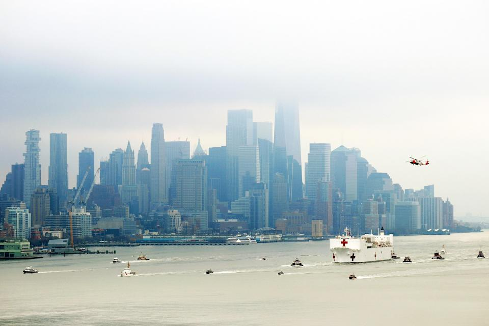 "A Coast Guard helicopter flies over the USNS <em>Comfort</em> hospital ship as it arrives to New York on March 30. The ship's 1,000 beds and 12 operation rooms were intended to take non-COVID patients to ease the pressure on New York hospitals. However, the ship only welcomed <a href=""https://www.nytimes.com/2020/04/02/nyregion/ny-coronavirus-usns-comfort.html"" rel=""nofollow noopener"" target=""_blank"" data-ylk=""slk:20 patients"" class=""link rapid-noclick-resp"">20 patients</a> after a week of operation, leading <a href=""https://www.npr.org/sections/coronavirus-live-updates/2020/04/06/827995726/in-new-york-overflow-hospitals-at-javits-and-on-navy-ship-have-been-largely-empt"" rel=""nofollow noopener"" target=""_blank"" data-ylk=""slk:Governor Andrew Cuomo to suggest opening"" class=""link rapid-noclick-resp"">Governor Andrew Cuomo to suggest opening</a> the makeshift hospital to coronavirus patients as well."