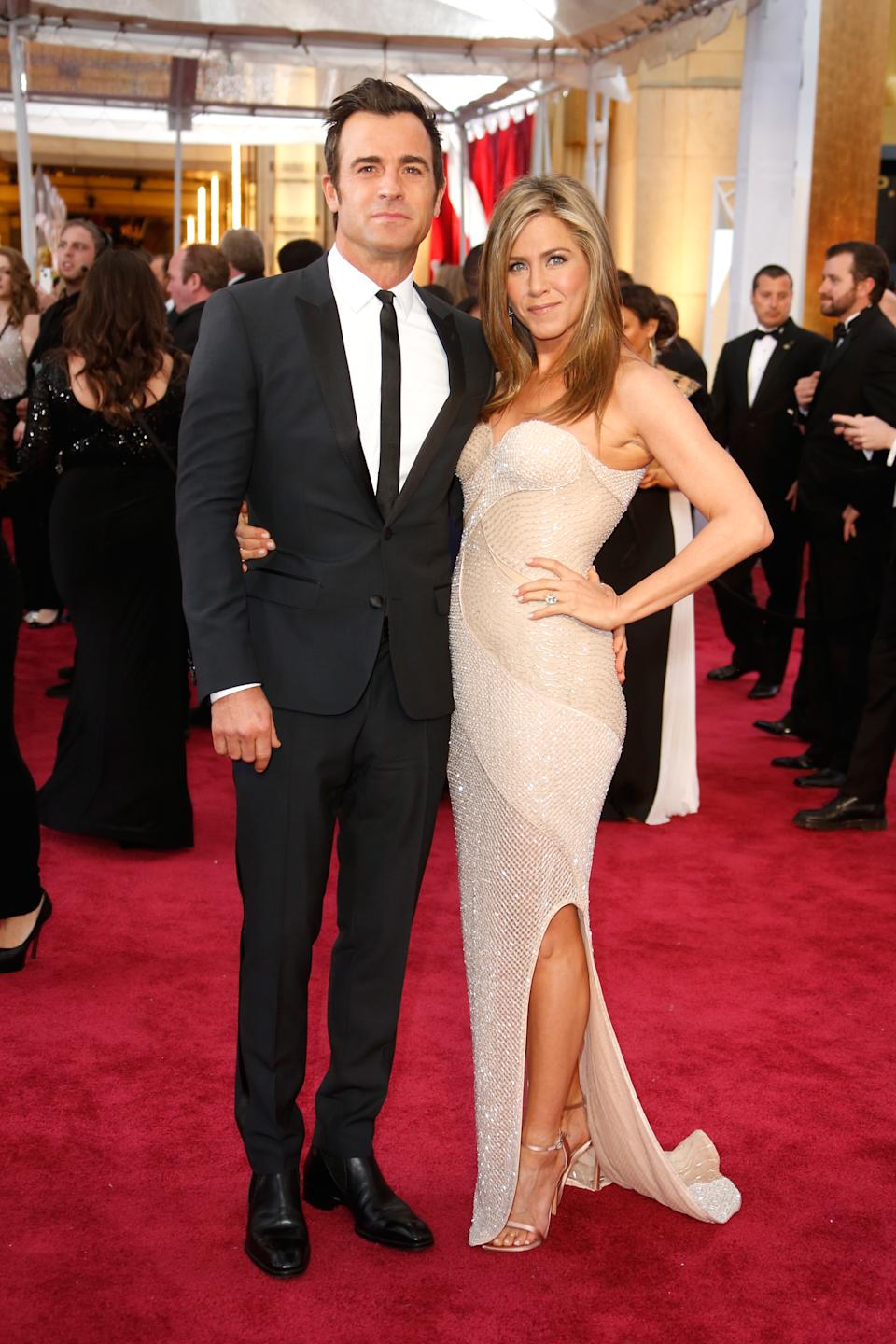 Aniston was the picture of Hollywood glamour in a sparkling Versace gown with then-fiancé Justin Theroux at the 87th Academy Awards in 2015. (Image via Getty Images)