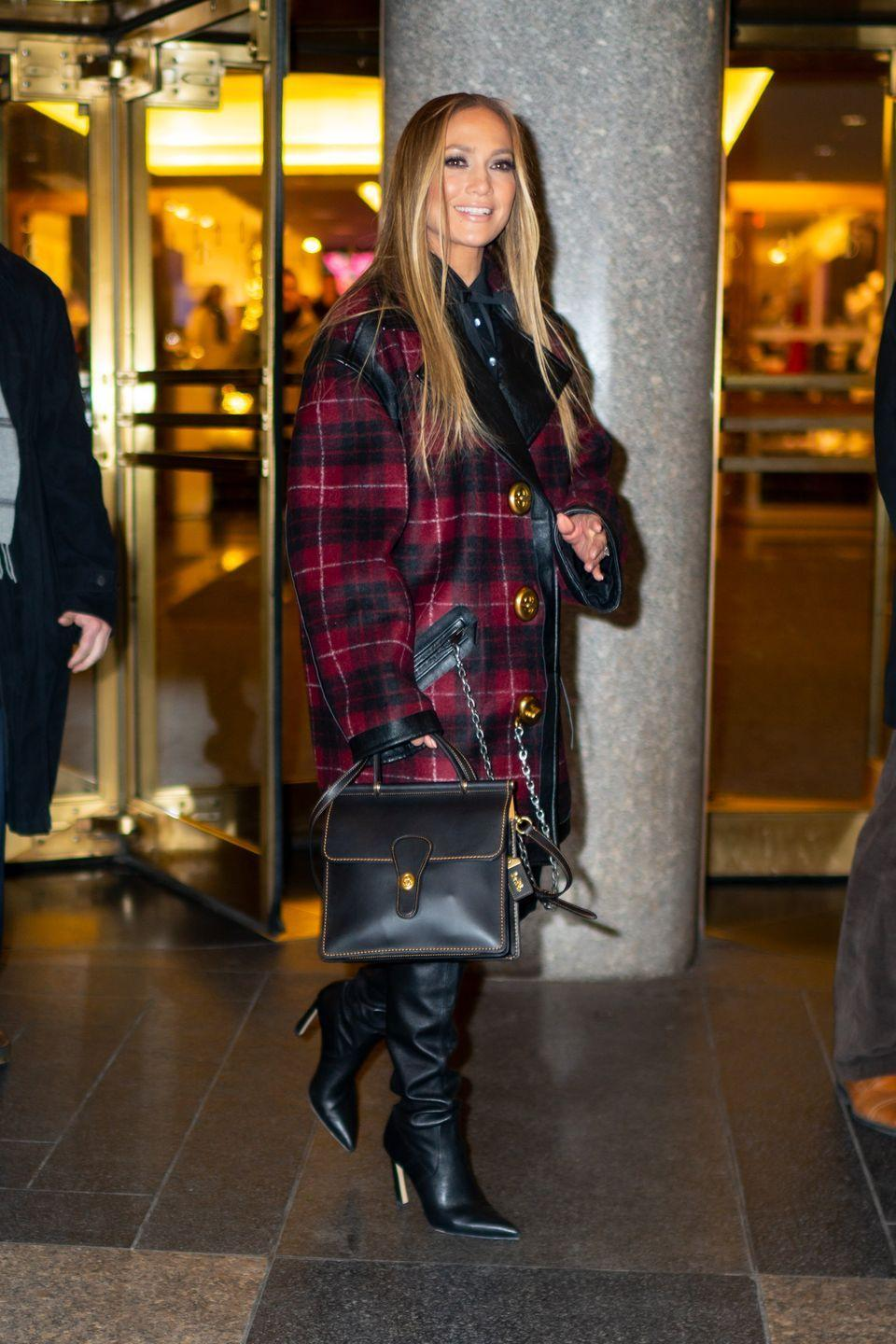 <p>The star wore a tartan oversized coat and chic leather-look books to brave the chilly NYC December temperatures.</p>