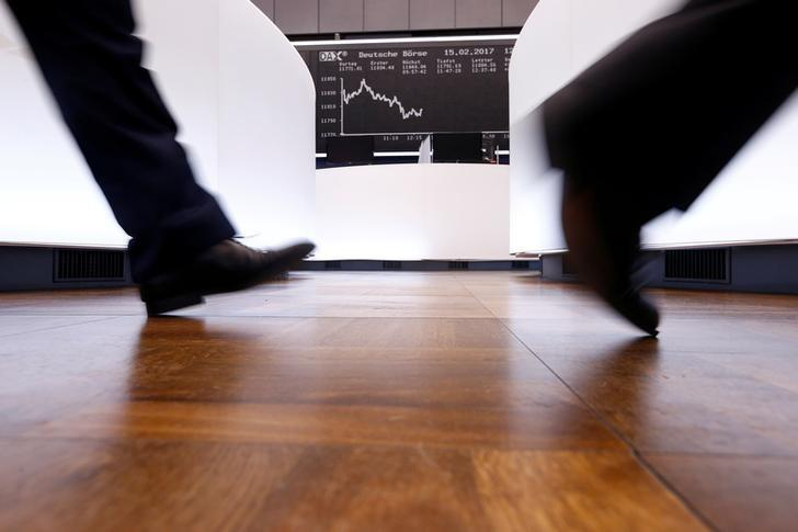 FILE PHOTO: A trader walks past the German DAX Index board on the trading floor at the Frankfurt stock exchange in Frankfurt, Germany February 15, 2017. REUTERS/Ralph Orlowski/File Photo