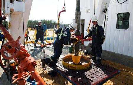 FILE PHOTO: Oil rig floorhands work on an oil rig at the Cenovus Energy Christina Lake SAGD project south of Fort McMurray