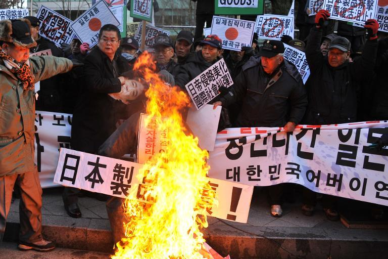 South Korean conservative activists set fire to effigies of Japanese Prime Minister Shinzo Abe during a protest to lodge a complaint against Abe visiting the Yasukuni war shrine, in Seoul on December 27, 2013