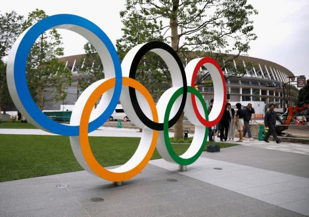 FILE PHOTO: Olympic rings are displayed in front of the construction site of the New National Stadium, the main stadium of Tokyo 2020 Olympics and Paralympics, during a media opportunity in Tokyo