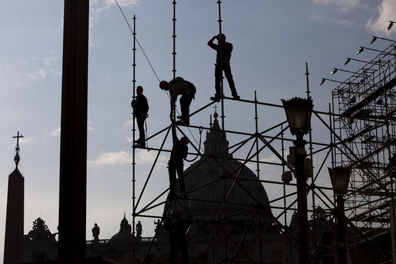 "Workers climb down scaffolding set up for video screens in front of St. Peter's Basilica, ahead of Pope Benedict XVI's last general audience, scheduled for Wednesday, at the Vatican, Tuesday, Feb. 26, 2013. Pope Benedict XVI will be known as ""emeritus pope"" in his retirement and will continue to wear a white cassock, the Vatican announced Tuesday, again fueling concerns about potential conflicts arising from having both a reigning and a retired pope.The pope's title and what he would wear have been a major source of speculation ever since Benedict stunned the world and announced he would resign on Thursday, the first pontiff to do so in 600 years. (AP Photo/Oded Balilty)"
