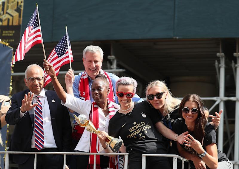 NEW YORK, NEW YORK - JULY 10: (l-R) President of the USA Soccer Federation Carlos Cordeiro, New York Mayor Bill de Blasio, his Wife Chirlane McCray, Megan Rapinoe, Allie Long, and Alex Morgan celebrate during the U.S. Women's National Soccer Team Victory Parade and City Hall Ceremony on July 10, 2019 in New York City. (Photo by Al Bello/Getty Images)