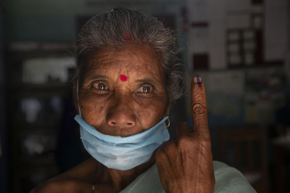 An elderly tribal Mishing displays the indelible ink on her finger after casting her vote at a polling center during the first phase of Assam state elections in Majuli, India, Saturday, March 27, 2021. Voting began Saturday in two key Indian states with sizeable minority Muslim populations posing a tough test for Prime Minister Narendra Modi's popularity amid a months-long farmers' protest and the economy plunging with millions of people losing jobs because of the coronavirus pandemic. (AP Photo/Anupam Nath)