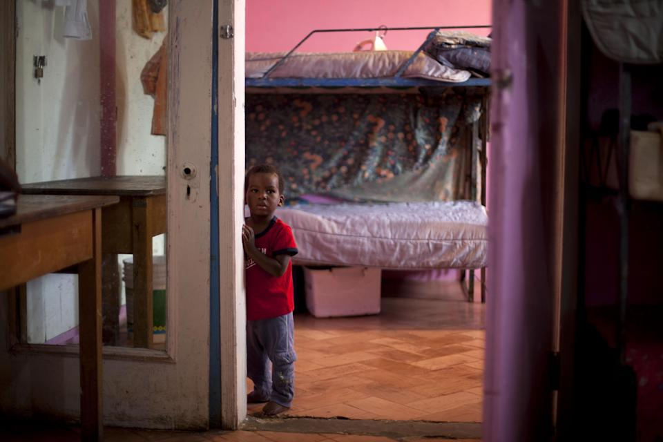 In this Nov. 13, 2013 photo, a young boy stands in his room in the U.S.-based Church of Bible Understanding orphanage in Kenscoff, Haiti. The orphanage is run by a Christian missionary group funded by the Olde Good Things antique store on Manhattan's Upper West Side. While many other orphanages also have failed the Caribbean country's new national standards, and conditions are far worse in some, the group's three-story building on the hilly outskirts of Port-au-Prince stands out because it's run by an organization with such an unusual, and successful fundraising operation. The failure to meet the standards would seem to contradict their financial position.(AP Photo/Dieu Nalio Chery)