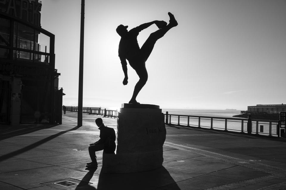 A man sits beneath a statue of San Francisco Giants Hall of Fame pitcher Juan Marichal outside Oracle Park and looks out to McCovey Cove in San Francisco on April 24, 2020. Normally, the months leading into summer bring bustling crowds to the city's famous landmarks, but this year, because of the coronavirus threat they sit empty and quiet. Some parts are like eerie ghost towns or stark scenes from a science fiction movie. (AP Photo/Eric Risberg)