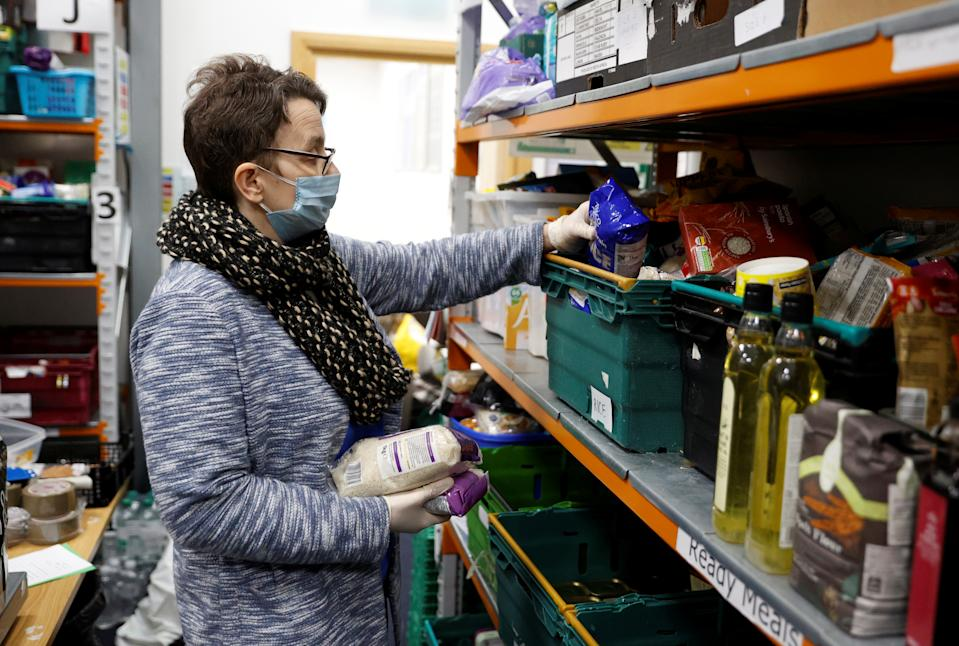 A volunteer at the North Enfield Foodbank Charity packs a bag of groceries and other household items for distribution in Enfield as the spread of coronavirus disease (COVID-19) continues in London, Britain March 24, 2020. REUTERS/John Sibley