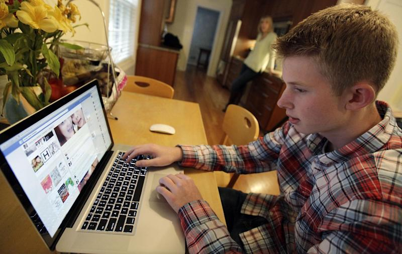 In this Oct. 24, 2013 photo, Mark Risinger, 16, checks his Facebook page on his computer as his mother, Amy Risinger, looks on at their home in Glenview, Ill. The recommendations are bound to prompt eye-rolling and LOLs from many teens but an influential pediatrician's group says unrestricted media use has been linked with violence, cyber-bullying, school woes, obesity, lack of sleep and a host of other problems. Mark's mom said she agrees with restricting kids' time on social media but that deciding on other media limits should be up to parents. (AP Photo/Nam Y. Huh)