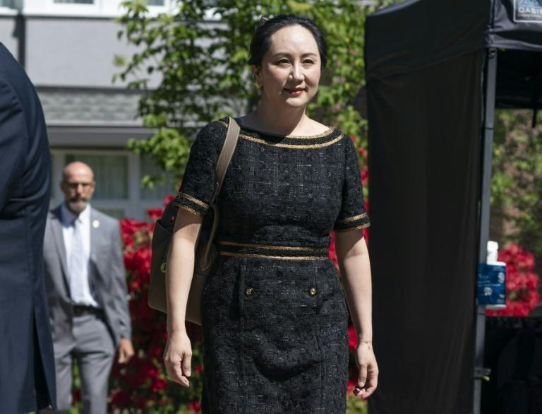 Meng Wanzhou, CFO of Huawei, walks down her driveway to her car as she departs her home for court on May 27, 2020 in Vancouver, Canada (AFP Photo/Rich Lam)