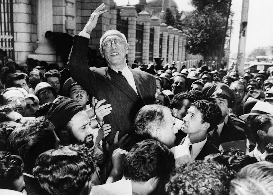 Iranian Prime Minister Mohammad Mosaddegh rides on the shoulders of cheering crowds.