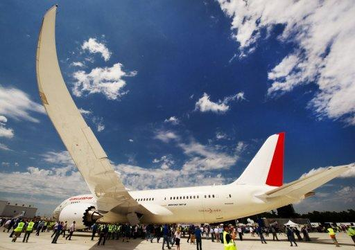 Employees take photos after the new Boeing 787 Dreamliner built for Air India is rolled-off the production line