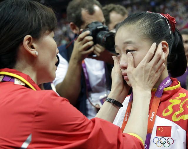 Chinese gymnast Sui Lu is consoled by her coach during the artistic gymnastics women's apparatus finals for the balance beam at the 2012 Summer Olympics, Tuesday, Aug. 7, 2012, in London. (AP Photo/Julie Jacobson)