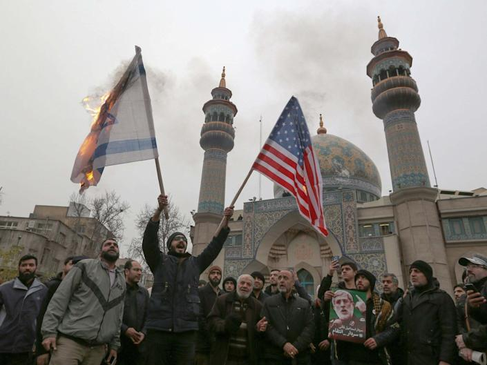 Israeli and a US flag are burned during protest over the killings of Iranian general Qasem Soleimani and Iraqi paramilitary chief Abu Mahdi al-Muhandis in an American airstrike: AFP via Getty Images