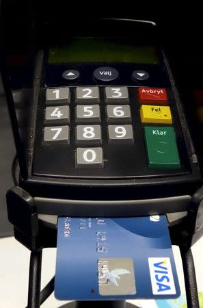 A credit card is seen inserted in a card reader at a store in Stockholm