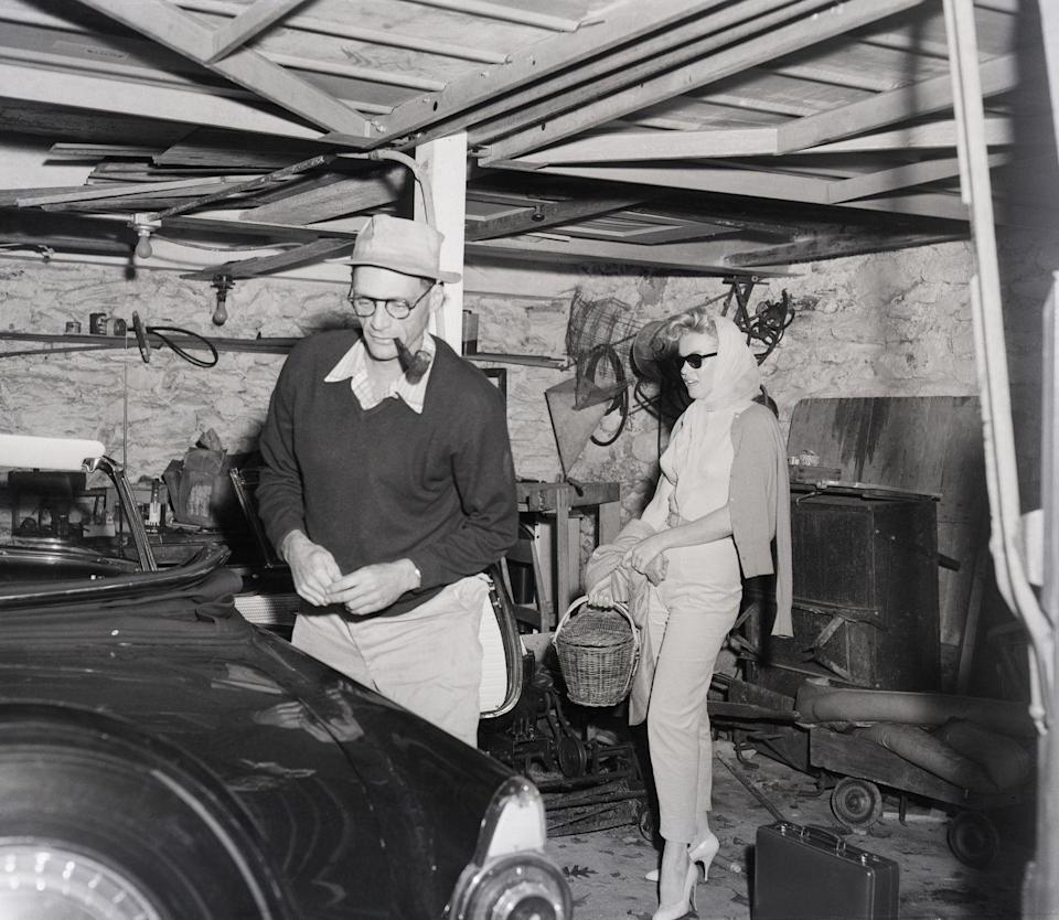 <p>The glamorous film star's garage appears as any other, with miscellaneous items strewn about. Marilyn and Arthur are making their way to their convertible in 1956. </p>