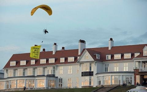 """<span>A Greenpeace protester flying a microlight passes over Donald Trump's resort in Turnberry with a banner reading """"Trump: Well Below Par""""</span> <span>Credit: John Linton/PA </span>"""