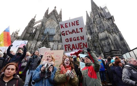"A man holds up a sign reading ""No violence against women"" as he takes part in a demonstration in front of the cathedral in Cologne - Credit: ROBERTO PFEIL/AFP"