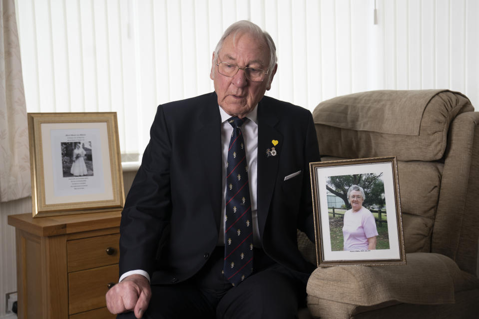 Gordon Bonner holds a photograph of his wife Muriel who, in April 2020 died of COVID-19, at his home in Leeds, England Saturday Jan. 23, 2021. Bonner, 86, is just one of many hundreds of thousands of Britons toiling with grief because of the pandemic. With more than 2 million dead worldwide, people the world over are mourning loved ones, but the U.K.'s toll weighs particularly heavily: It is the smallest nation to pass the 100,000 mark. ( AP Photo/Jon Super)