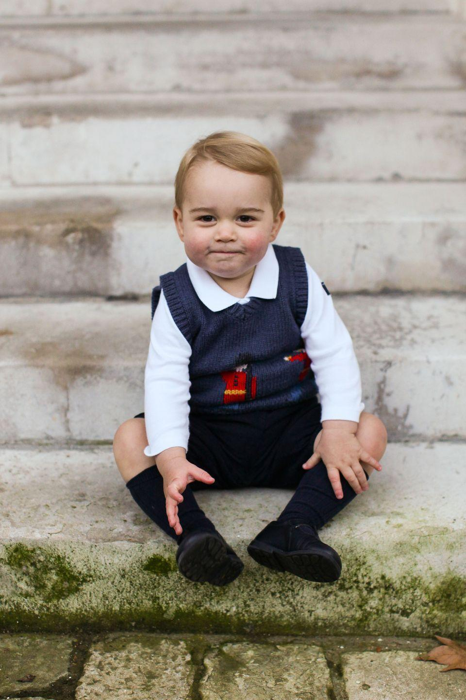 <p>Prince George sits on the steps of Kensington Palace ahead of his first-ever Christmas with the royal family in December 2014. The photo, which features George in a jumper with a guardsman pattern, was part of a trio taken by Prince Harry's private secretary Edward Lane Fox.</p>