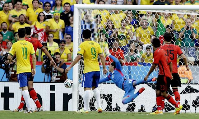 Mexico's goalkeeper Guillermo Ochoa, center, makes a save during the group A World Cup soccer match between Brazil and Mexico at the Arena Castelao in Fortaleza, Brazil, Tuesday, June 17, 2014. (AP Photo/Andre Penner)