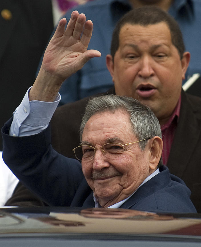 Cuban President Raul Castro waves to the press, next to Venezuelan President Hugo Chavez (behind) whilst leaving following the ALBA summit, at the Miraflores presidential palace in Caracas, on February 5, 2012 (AFP Photo/Juan Barreto)