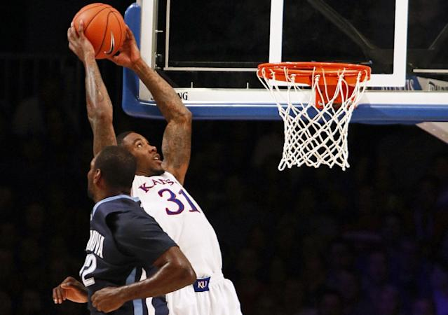Kansas' Andrew White III, right, drives for a dunk as Villanova's Jay Vaughn looks on during the first half of an NCAA college basketball game in Paradise Island, Bahamas, Friday, Nov. 29, 2013. (AP Photo/Bahamas Visual Services, Dante Carrer)