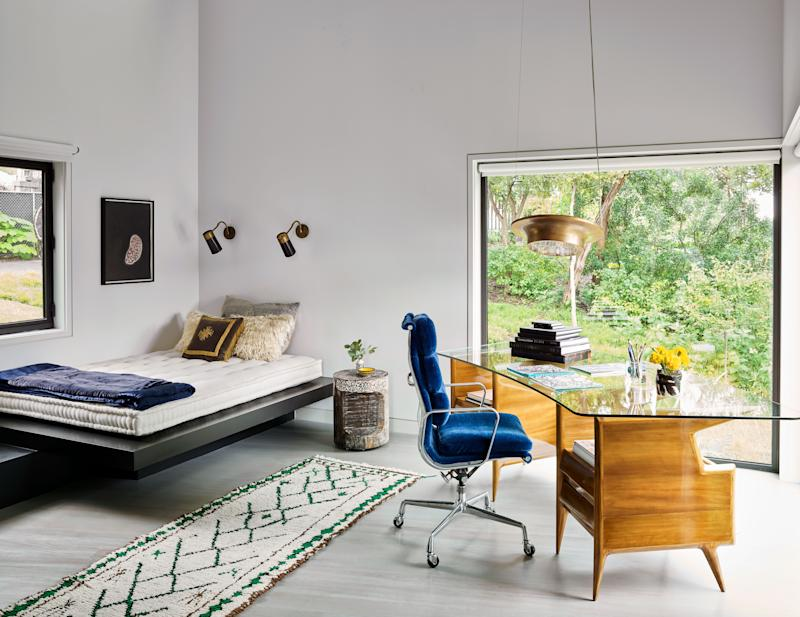 A glass-topped desk designed by Gio Ponti dominates a cantilevered office area off the kitchen; it sits opposite a custom bed platform highlighted by Yayoi Kusama artwork.