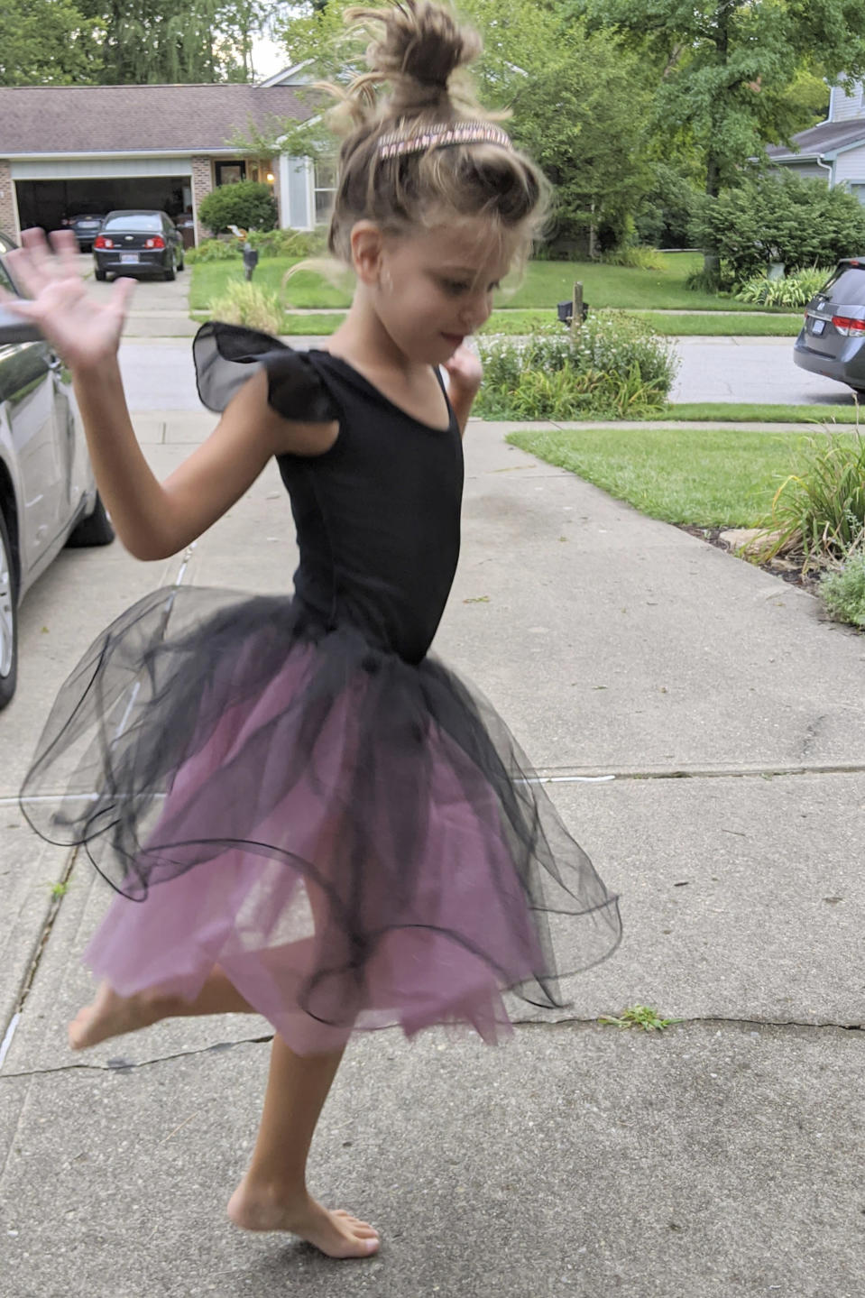 In this photo provided by courtesy of Nancy Peters, Margaret (Maggie) Hoying performs for her grandparents in the driveway after her dance recital which was cancelled due to the coronavirus, in August 2020, in Cincinnati. The pandemic and its isolating restrictions have been especially tough for many of the nation's some 70 million grandparents, many at ages when they are considered most vulnerable to the deadly COVID-19 virus. (Nancy Peters via AP)