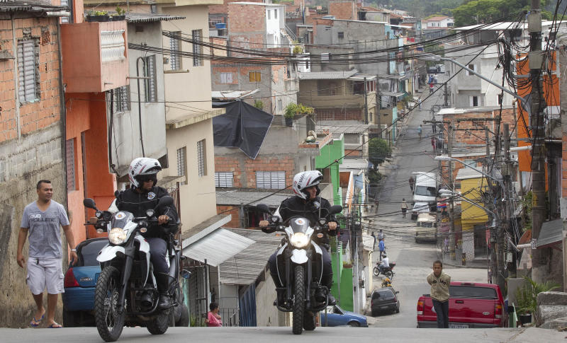 Motorcycle policemen patrol the Paraisopolis slum in Sao Paulo, Brazil, Friday, Nov. 2, 2012. Authorities say that members of a powerful drug gang are stirring violence in South America's largest city, retaliating against increased arrests of traffickers. Nearly 90 police have been killed in Sao Paulo this year, most being targeted while they were off duty. (AP Photo/Andre Penner)