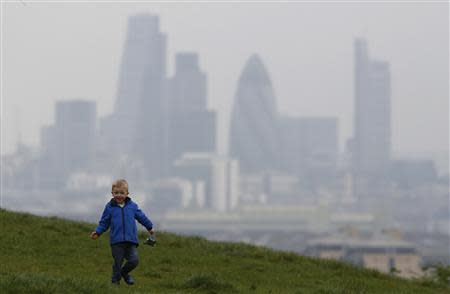 Daniel Buttery, 4, plays in Greenwich Park as a haze of pollution sits over the London skyline April 3, 2014. REUTERS/Luke MacGregor