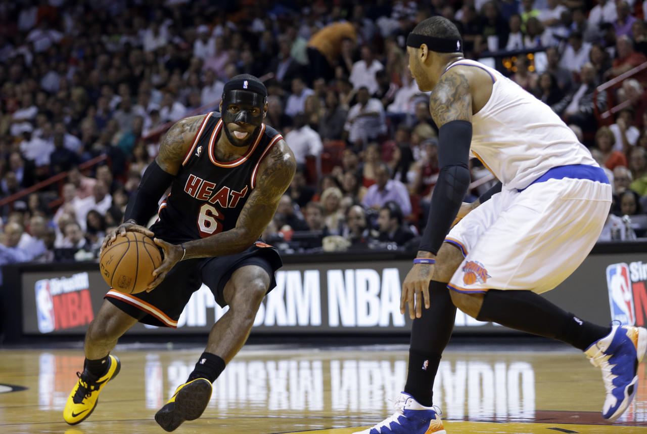 Miami Heat small forward LeBron James (6) drives as New York Knicks small forward Carmelo Anthony (7) defends during the first half of an NBA basketball game in Miami, Thursday, Feb. 27, 2014. (AP Photo/Alan Diaz)