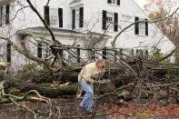 John Constantine makes his way out of his house after winds from Hurricane Sandy toppled a tree fell onto it in Andover, Mass. Monday, Oct. 29, 2012. Hurricane Sandy continued on its path Monday, as the storm forced the shutdown of mass transit, schools and financial markets, sending coastal residents fleeing, and threatening a dangerous mix of high winds and soaking rain. (AP Photo/Winslow Townson)