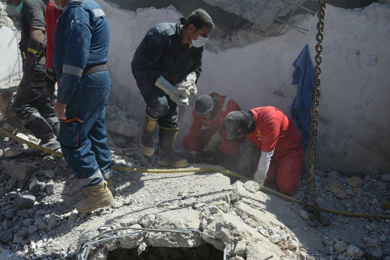 Iraqi firefighters search for bodies buried under the rubble, of civilians who were killed after an air strike against Islamic State triggered a massive explosion in Mosul, Iraq March 27, 2017. REUTERS/Stringer