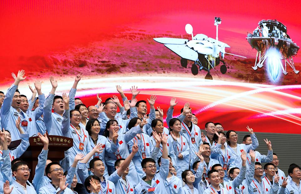 In this photo released by Xinhua News Agency, members at the Beijing Aerospace Control Center celebrate after China's Tianwen-1 probe successfully landed on Mars.