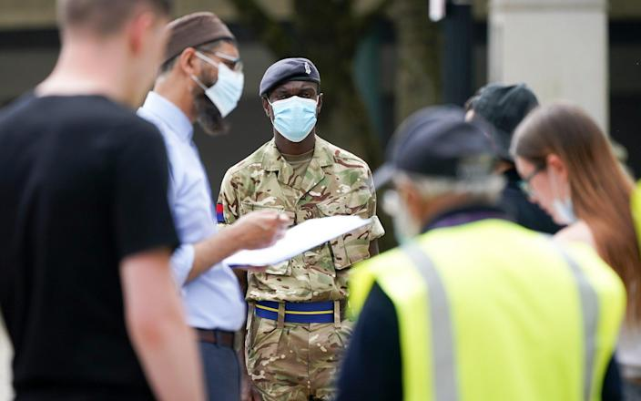 Soldiers from the Royal Horse Artillery guide members of the public at a rapid vaccination centre, set up outside Bolton Town Hall - Getty