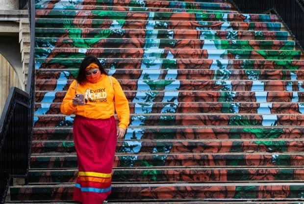 A woman wearing a mask and an 'Every Child Matters' sweater descends a set of stairs near Confederation Park in Ottawa on Sept. 30, 2021, the first National Day for Truth and Reconciliation. (Trevor Pritchard/CBC - image credit)
