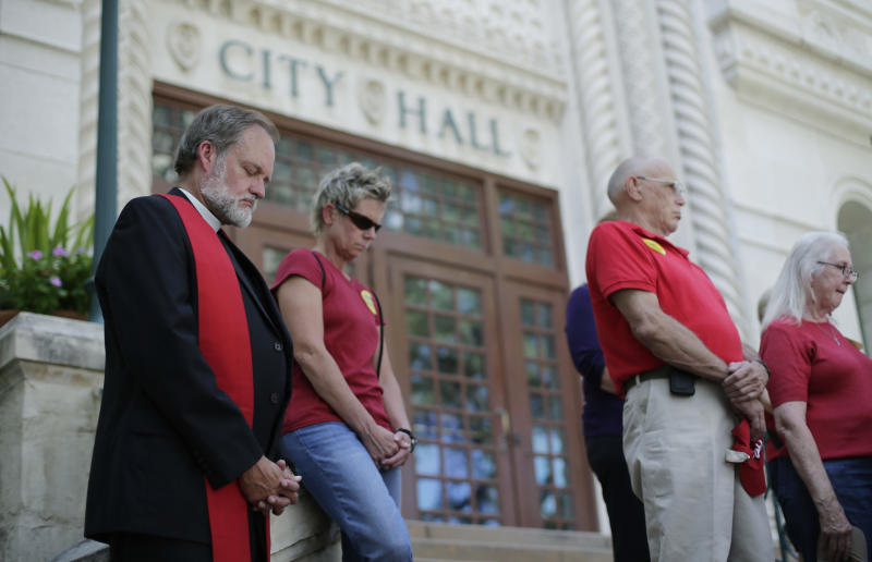 Pastor Paul Ziese, left, prays with other Faith leaders who support a proposed non-discrimination ordinance on the steps of City Hall, Tuesday, Sept. 3, 2013, in San Antonio. The San Antonio city council will vote Thursday on the ordinance which in part would prohibit discrimination based on sexual orientation and gender identity. (AP Photo/Eric Gay)