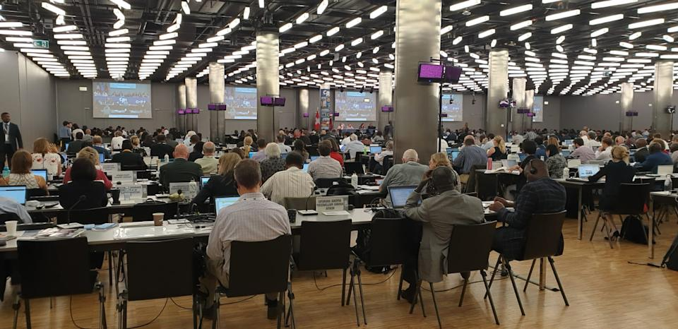 Shot from behind, a room full of people sitting at rows of desks with screens in the background.