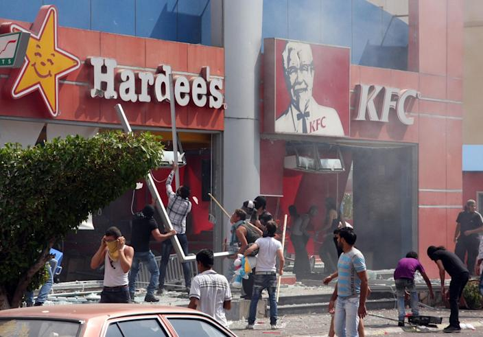 Lebanese protesters attack American fast food restaurants after Friday prayers in the northeastern city of Tripoli, Lebanon, Friday, Sept. 14, 2012. According to security officials no one was hurt in the attack which is part of widespread anger across the Muslim world about a film ridiculing Islam's Prophet Muhammad. (AP Photo)