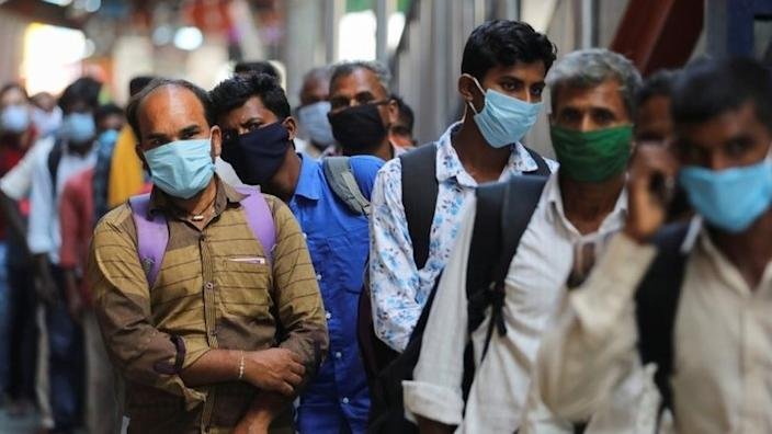 Passengers wearing protective face masks stand in a queue on a platform to get tested for the coronavirus disease (COVID-19), at a railway station, in New Delhi, India, October 5, 2020.