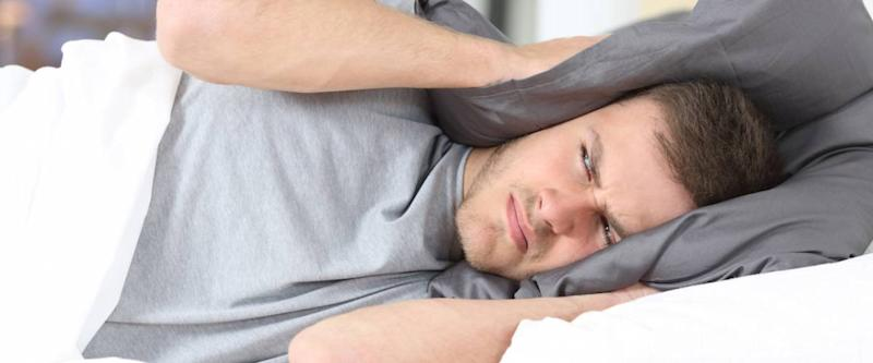 One man trying to sleep covering ears to avoid neighbor noise at home