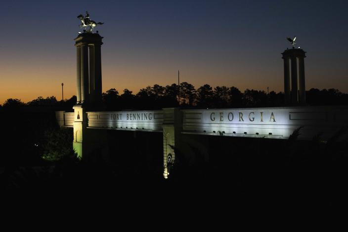 A bridge marks the entrance to the U.S. Army's Fort Benning as the sun rises in Columbus, Ga. Fort Benning is named after Confederate officers.