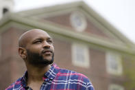 """Brown University graduate Jason Carroll, a Maryland native whose ancestors were slaves in the Carolinas, stands for a portrait on the Brown campus in Providence, R.I., on Tuesday, May 4, 2021, near University Hall, background, that was constructed in part using slave labor. """"There's real trauma and pain here,"""" says Carroll. """"This shouldn't just be an academic question. There are real families that have been burdened and harmed by this — and probably still are."""" (AP Photo/Steven Senne)"""